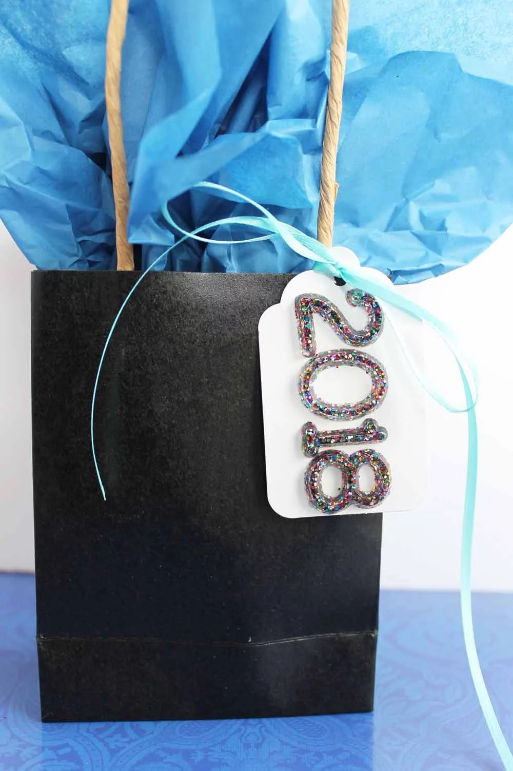 black bag with blue tissue paper and gift tag that has multicolor glitter resin numbers