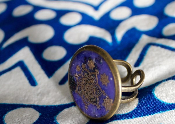 Close-up of ring with gold mandala designs on deep purple resin background
