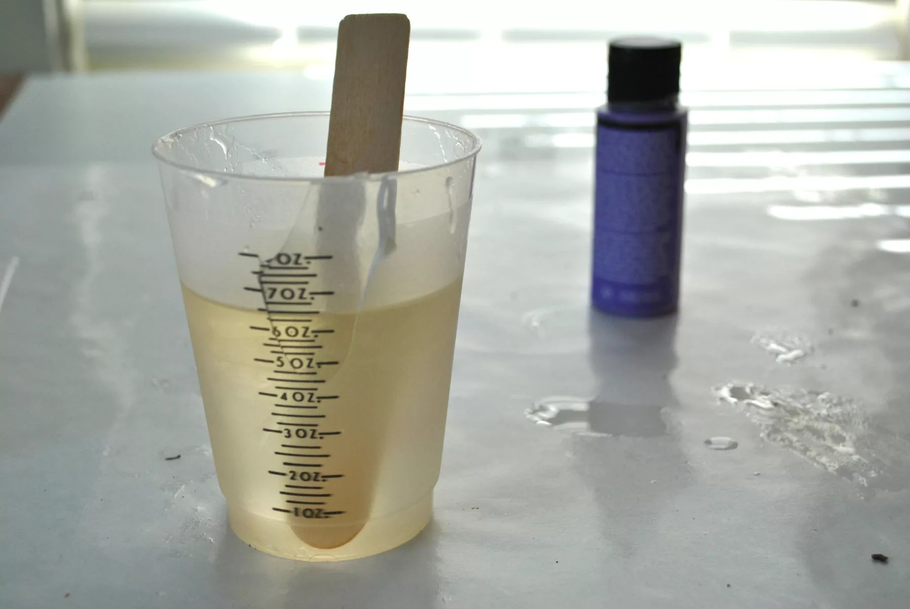 resin mixture in plastic measuring cup with wooden stirrer and resin dye on a table