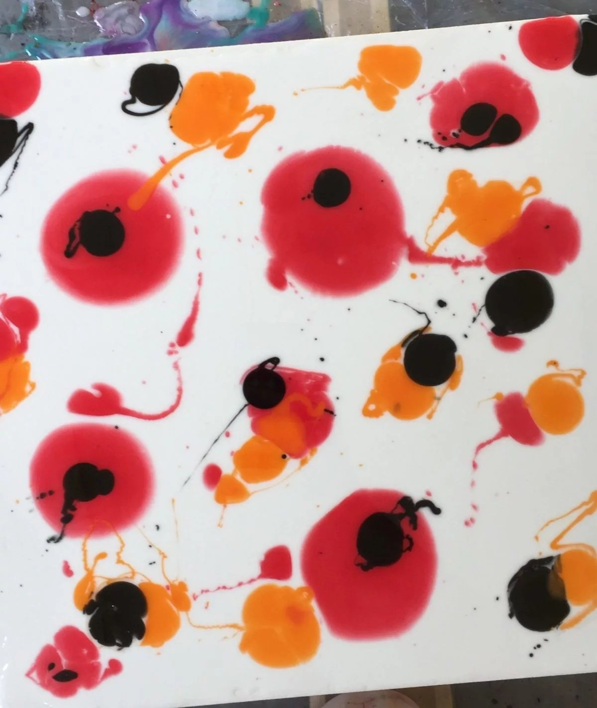 red orange and black resin on a white painting