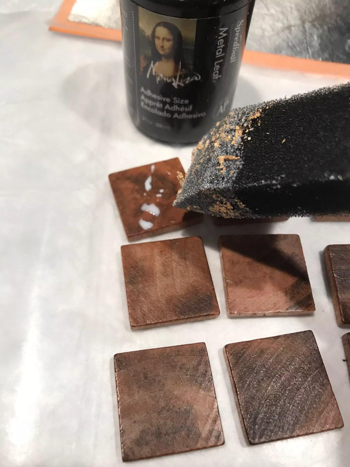 adding modge podge to wooden tile