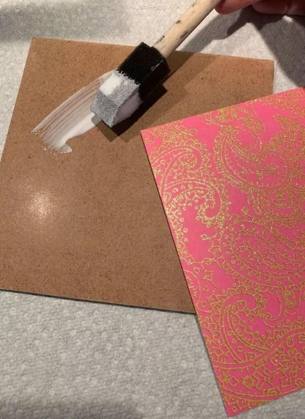 brushing glue on resin clock backing for card stock