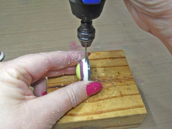 drilling a hole in a resin charm on a wood block