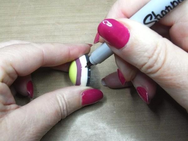 hands displaying where to mark hole on resin charm for drilling
