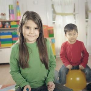 Photo de deux jeunes enfants assis sur des balles rebondissantes ans une crèche