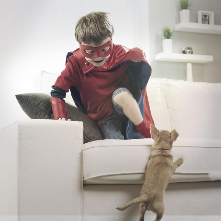 Photo d'un jeune garçon en costume de super héro qui joue avec son chien dans le salon