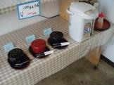 とある店舗の100円沖縄そば②(トッピングの具の入った容器とだし汁の入ったポット)