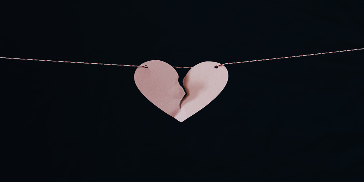A pink paper heart, torn down the middle hangs from a thread against a jet black background