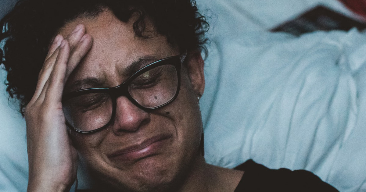A woman of colour sits by her bed, her hand held to her head looking deeply distressed