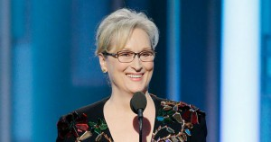 Meryl Streep standing behind a microphone smiling. She is wearing a black dress with many colorful, light-reflecting jewels.