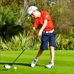 Tommy Morrissey, who has just one arm, golfing wearing blue shorts and a red collared shirt and baseballcap