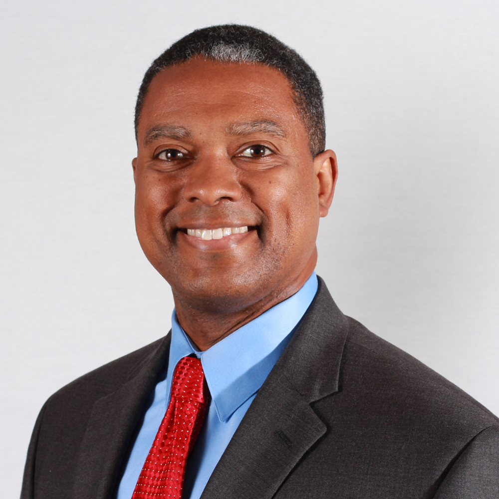 headshot of Gerard Robinson smiling and facing the camera wearing a black suit blue shirt and red tie color photo