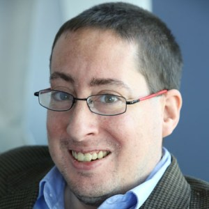 headshot of Justin Chappel wearing glasses color photo