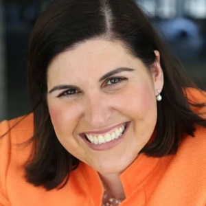 head shot of Lauren wearing an orange blazer, smiling and facing the camera color photo