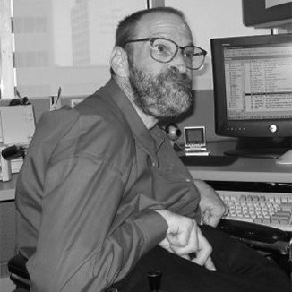 Neil Jacobson sitting at his computer and smiling he has a beard and is wearing glasses grayscale photo