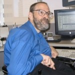 Neil Jacobson sitting at his computer and smiling he has a beard and is wearing glasses color photo