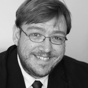 headshot of Philip Kahn Pauli wearing glasses with beard and mustache grayscale photo