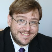 headshot of Philip Kahn Pauli wearing glasses and with beard and mustache color photo