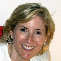 Shelley Cohen is smiling at the camera, her blonde hair is messy and she is wearing small earrings grayscale photo
