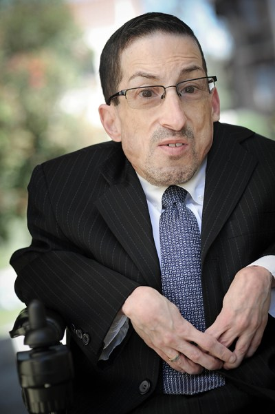 Steven James Tingus wearing a black suit and blue tie seated in his wheelchair outside