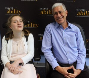 Lilly Grossman seated in her wheelchair and Richard Wolf seated in a chair smiling in front of a RespectAbility banner