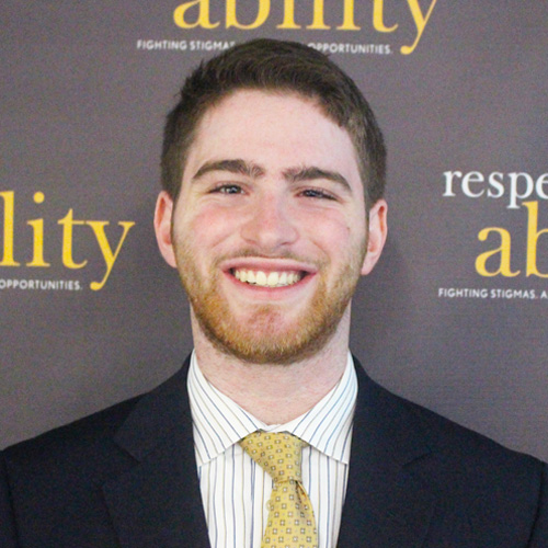 Respectability fellow Adam Fishbein smiling in front of the Respectability banner