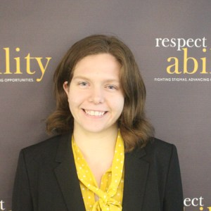 Respectability fellow Theresa Maher smiling in front of the Respectability banner