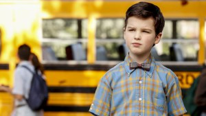 Nine-year-old Sheldon wearing a bow tie in front of a school bus