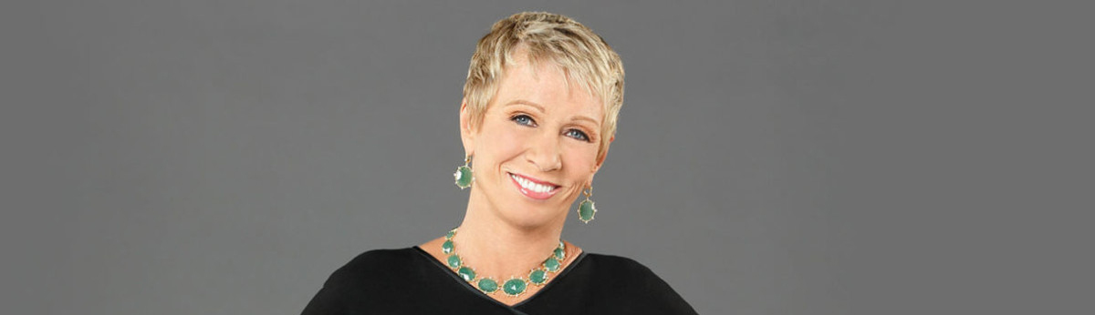 Barbara Corcoran standing with her hands at her hips posing for the camera wearing a black top and jade jewelry