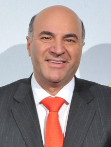 Kevin O'Leary headshot wearing a dark gray suit and a red tie