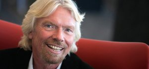 Richard Branson seated on a red couch, smiling and facing the camera