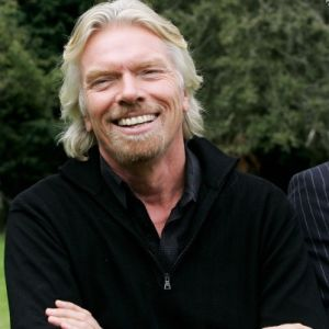Richard Branson smiling with arms crossed, wearing a black top
