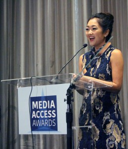 Atypical's Amy Okuda standing at a podium with the sign Media Access Awards
