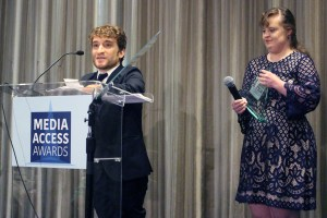 Nic Novicki and Jamie Brewer standing at a podium with the sign Media Access Awards