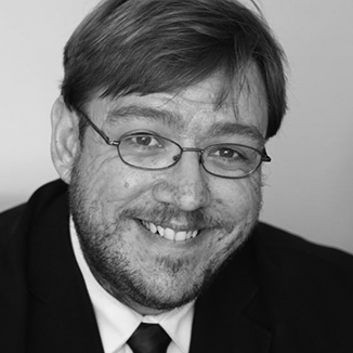 headshot of Philip Kahn-Pauli wearing a suit in grayscale