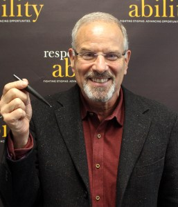 headshot of Stan Goldman smiling and holding a pen