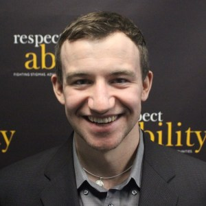 RespectAbility fellow Nicholas Olson smiling in front of the RespectAbility banner