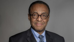 Clarence Page headshot wearing black suit, blue shirt and glasses