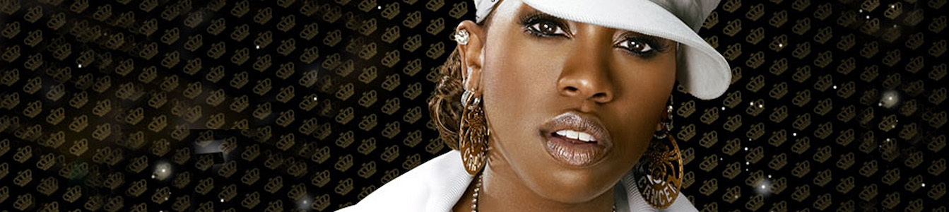 Close up of Missy Elliot posting for the camera wearing a white top and hat