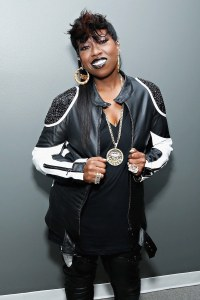Missy Elliot smiling for the camera, dressed in a black and white outift