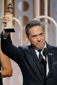 Lee Unkrich on stage holding an Oscar award