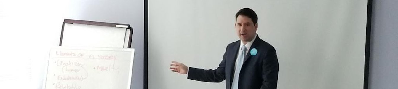 Geoffrey Melada standing in front of the room, pointing to a giant notepad