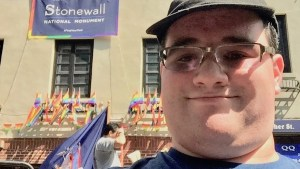 """Former RespectAbility Fellow Eric Ascher in front of the Stonewall Inn in New York City with a banner reading """"Stonewall National Monument #findyourpark"""""""