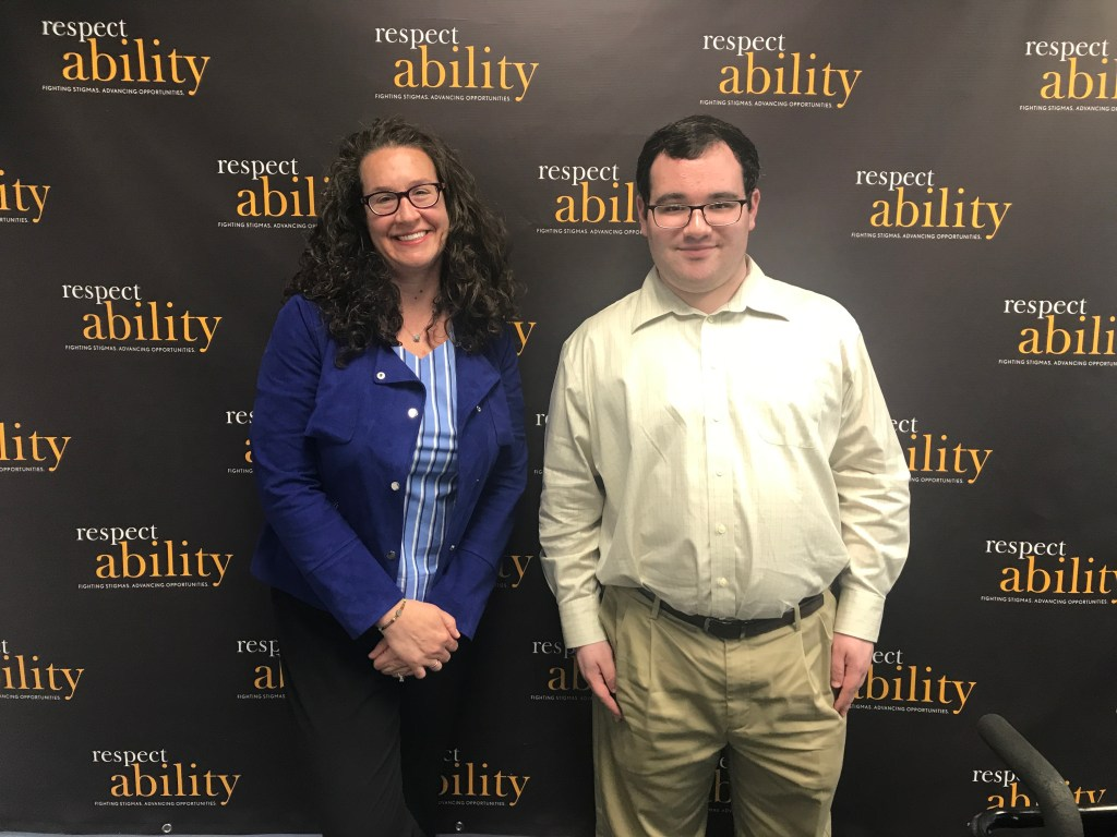 RespectAbility Board Member Dana Marlowe and RespectAbility Fellow Eric Ascher smiling in front of the RespectAbility banner