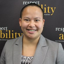 Headshot of Kaity in professional dress in front of the Respectability banner