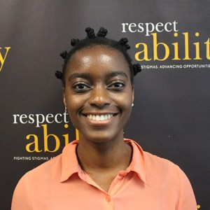 Victoria Grace Assokom-Siakam is smiling in front of the RespectAbility banner