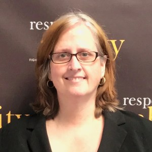 Kathleen L. Brockway smiling in front of the RespectAbility banner