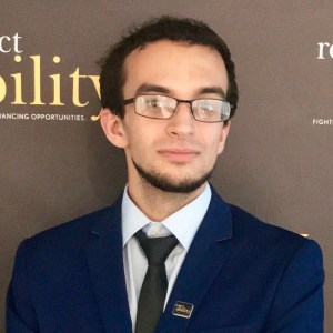 Zackary Tamimi smiling in front of the RespectAbility banner