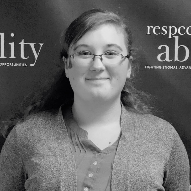 Emma Content smiling in front of the RespectAbility banner