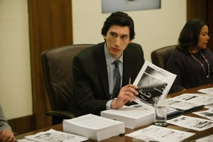 Adam Driver holding a paper with a photo on it, sitting at a desk with lots of papers on it